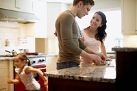 Young family preparing food in kitchen