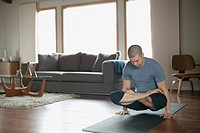 Man doing yoga poses at home.