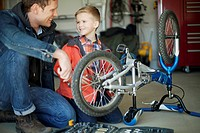 Father and young son repairing bicycle