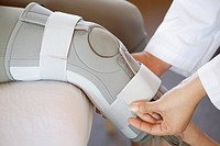 Doctor fastening knee brace on patient.