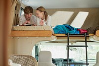 Siblings using computer technology in camper (thumbnail)