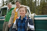 Three generations of males in front of old truck