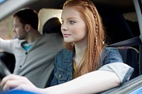 Young adult woman driving with friends