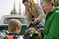 Three generations of men unloading gear from truck