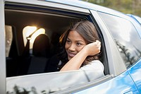 Young adult woman riding in the backseat of the car