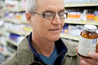 Man reading the labels at a drug store