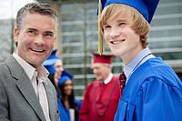 Male graduate with his father at graduation.