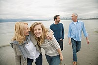 Mid-adult couple walking with parents on the beach (thumbnail)