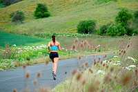 Young woman running in rural setting