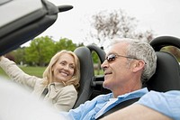 Middle_aged couple driving in a convertible