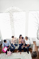 Family with two children 12-23 months, 2-3 and friends relaxing in living room (thumbnail)