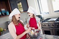 Sisters 13_15, 8_9 with fake mustache cooking in kitchen