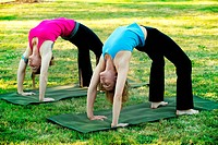 Two women bending over backwards on yoga mats outdoors