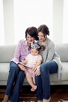 Grandmother, mother and daughter 2_3 sitting on sofa and looking at digital tablet