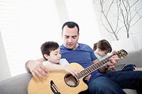 Father teaching son guitar while daughter uses technology