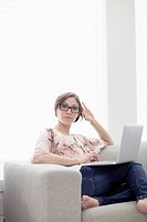 Portrait of a young woman at home holding a laptop