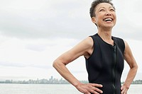 Middle-aged woman in wetsuit at the beach (thumbnail)