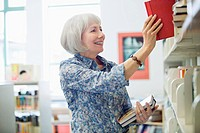Teacher returning books to shelf