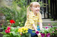 Cute, 5 year old girl planting flowers.