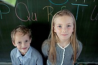 Schoolboy 6-7 and girl 8-9 posing in front of blackboard (thumbnail)