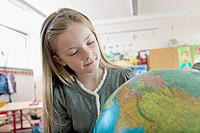 Happy young schoolgirl 8_9 looking at globe