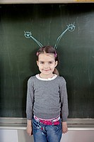 Young girl 6_7 standing in front of blackboard with insect feelers drawn on it
