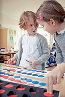 Boy 6-7 and girl 6-7 playing educational game (thumbnail)