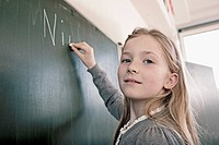 Happy young schoolgirl 8_9 writing on blackboard