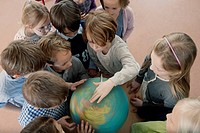 Group of school children 6_7 looking at globe