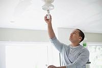 Young adult latino man replacing lightbulb