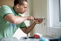 Young adult latino man replacing electrical outlet