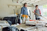 Father and son in the garage with discarded renovation materials