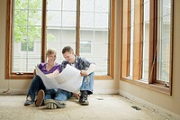 Mid adult couple reviewing building plans