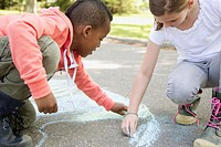 Elementary students creating sidewalk art with chalk