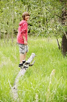 Middle school student standing on fallen tree branch