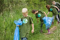 Elementary students picking up garbage in the park