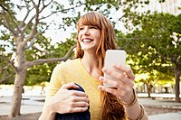Young woman using phone in park