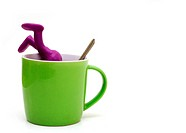 Purple puppet of plasticine sinking in cup