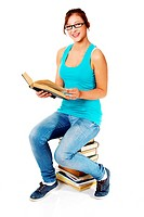 Young girl sitting on books and smiling.