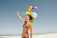Happy young woman with colourful balloons on sandy beach