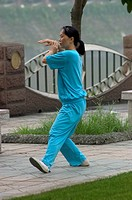 Chinese woman practices Tai Chi in a city park along the Jin River _ Chengdu, China in Sichuan Province