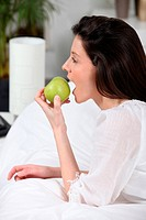 Young woman eating an apple laid on her bed