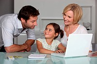 Parents and young daughter at laptop computer