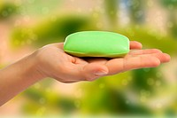 Green soap bar in hand on green abstract background.