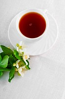 Teacup with saucer and jasmine flower on the white napkin