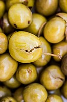 eigelegte grüne oliven, die mit einem stein zerquetscht wurden, um die marinade besser aufnehmen zu können, pickled olives that have been squashed wit...