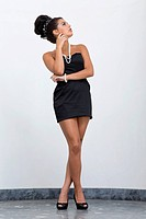 Young woman with an updo hairstyle wearing a short black dress and high heels