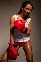 Studio shot of sexy female fighter with red boxing gloves