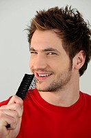 Young man singing into a hairbrush