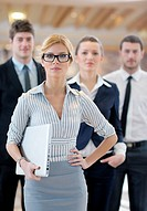 business woman standing with her staff in background at modern bright office conference room